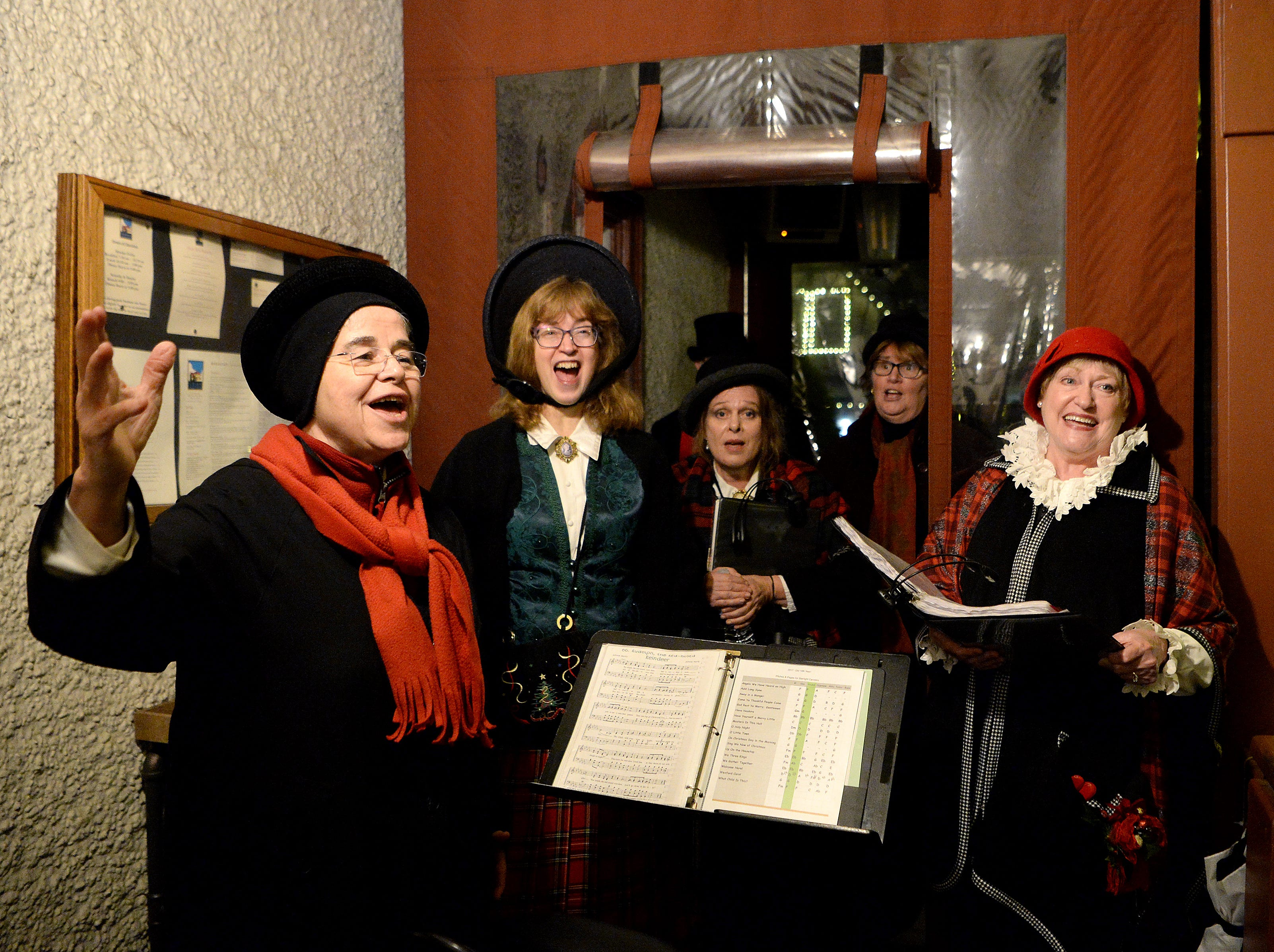 The Starlight Carolers perform on the porch of Corner Kitchen during the annual Biltmore Village Dickens Festival on Nov. 30, 2018. The singers have been performing for 11 years.