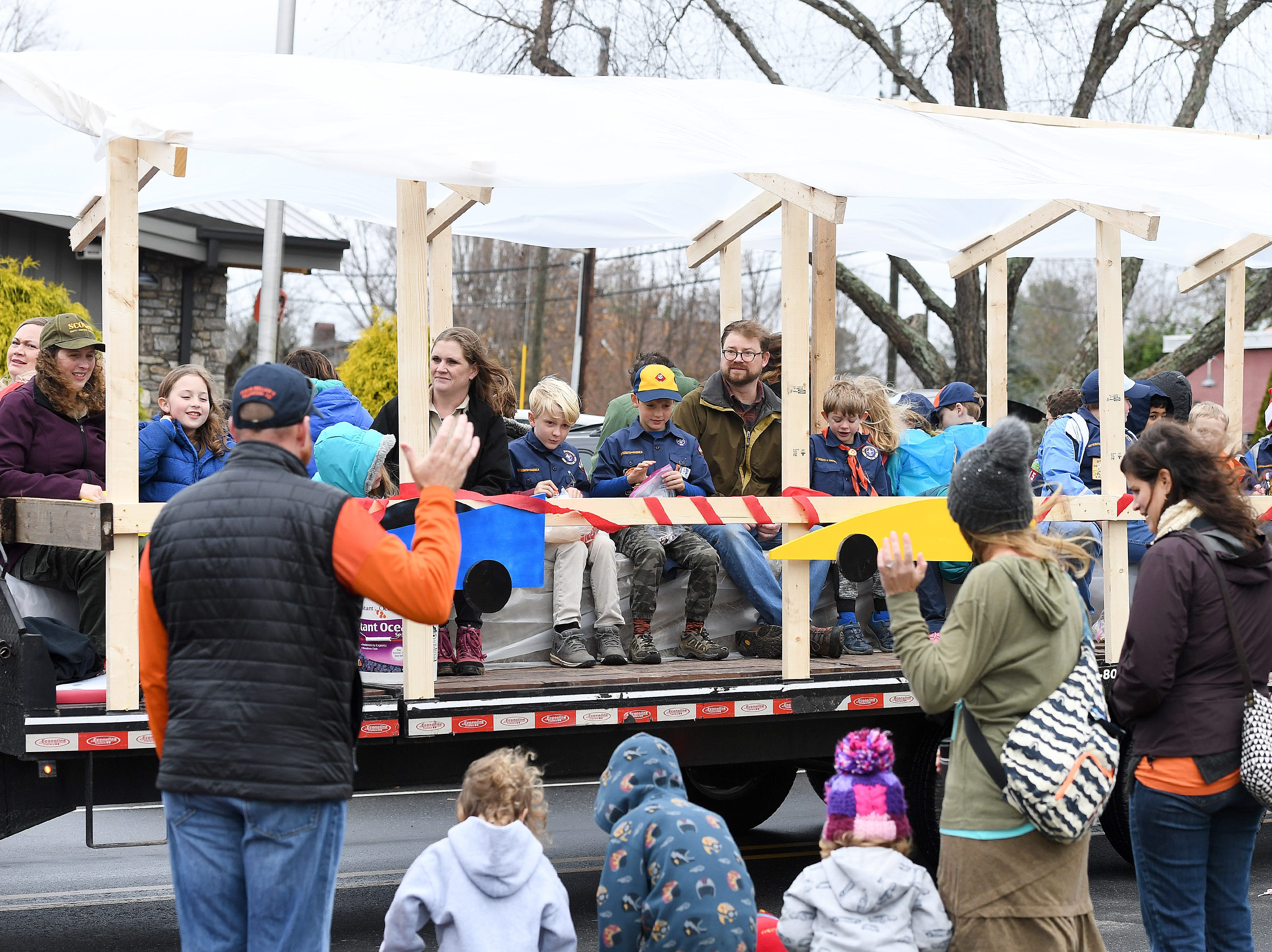 Cub Scouts and their families wave to people on the sidewalk from their float as they ride in the Weaverville Christmas Parade on Dec. 1, 2018.