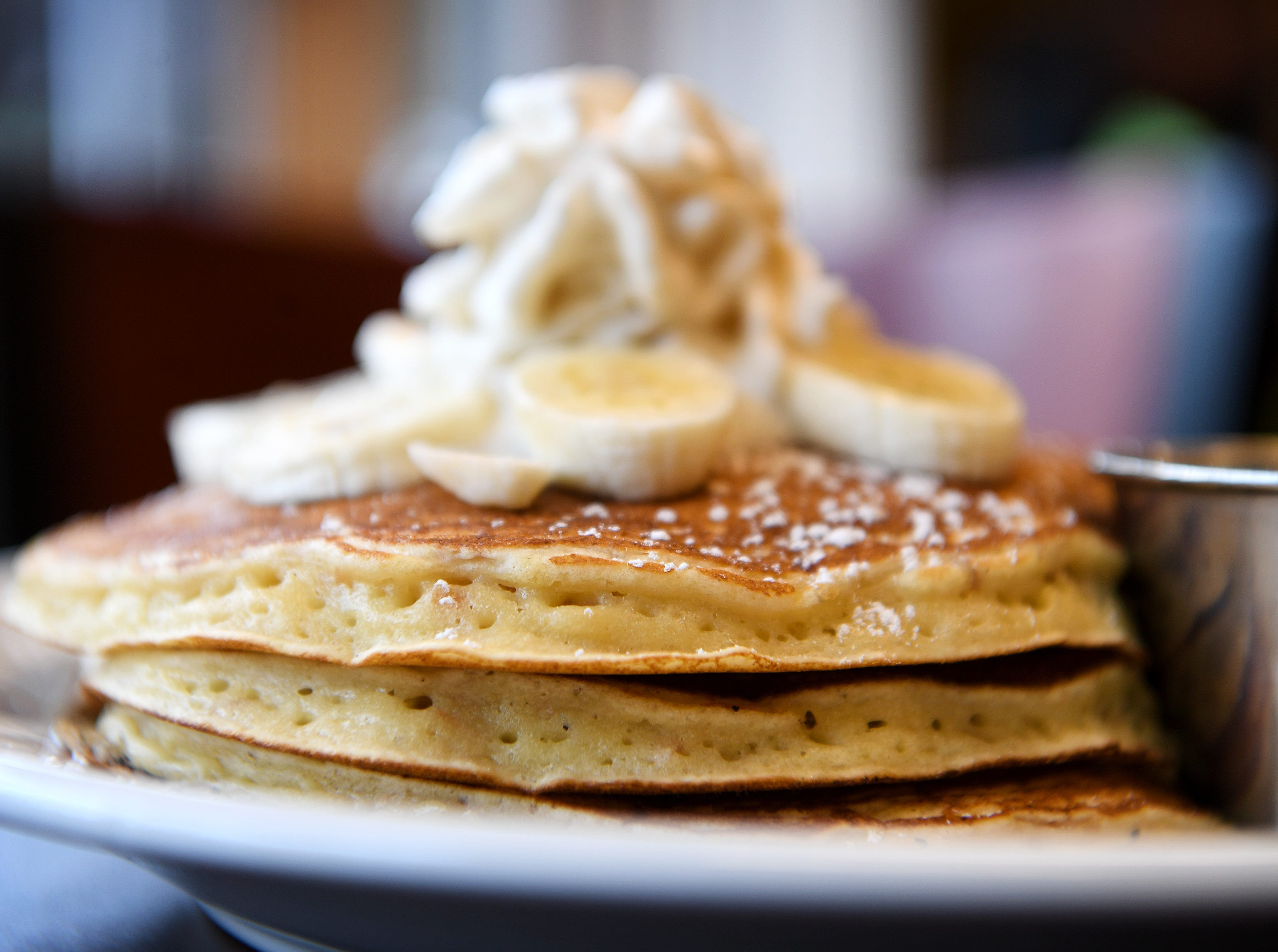 The ginger ricotta and coconut flakes pancakes at Abeja's House Cafe are topped with fresh bananas, whipped cream, and powder sugar and served with maple syrup on the side.