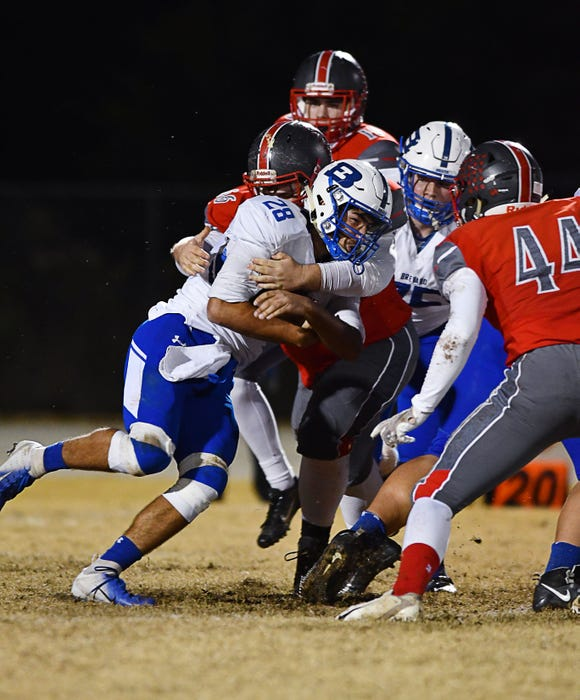 Brevard's Anthony Fields digs for yardage as Wheatmore's Tim Moser tries to bring him down Friday night