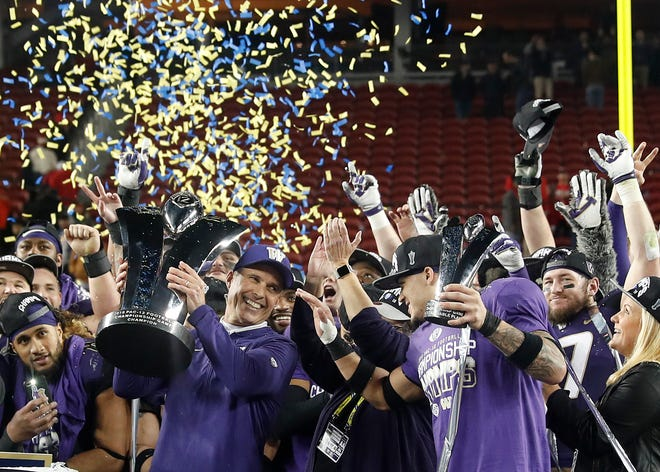 Washington coach Chris Petersen (left) and defensive back Byron Murphycelebrate after Washington defeated Utah 10-3 in the Pac-12 Conference championship.