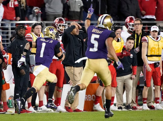 Washington defensive back Myles Bryant (5) celebrates as defensive back Byron Murphy (1) returns an interception for the game's only touchdown.