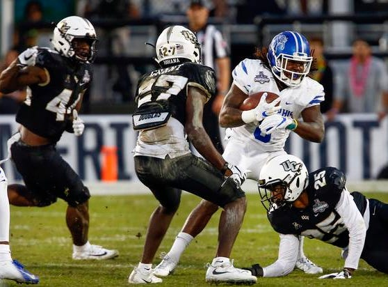 Memphis Tigers running back Darrell Henderson (8) is stopped by UCF Knights linebacker Nate Evans (44) and defensive back Richie Grant (27) and defensive back Kyle Gibson (25) during the second quarter at Spectrum Stadium.