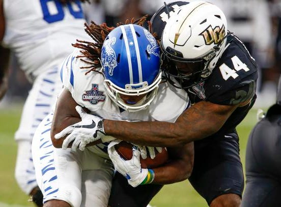 Memphis Tigers wide receiver Tony Pollard (1) is tackled by UCF Knights linebacker Nate Evans (44) during the second quarter at Spectrum Stadium.
