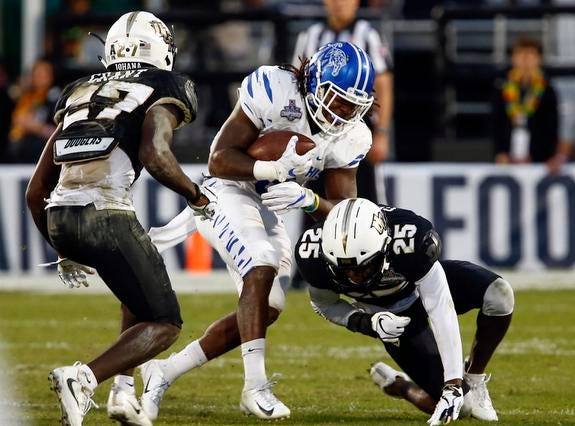Memphis Tigers running back Darrell Henderson (8) is stopped by UCF Knights defensive back Richie Grant (27) and defensive back Kyle Gibson (25) during the second quarter at Spectrum Stadium.