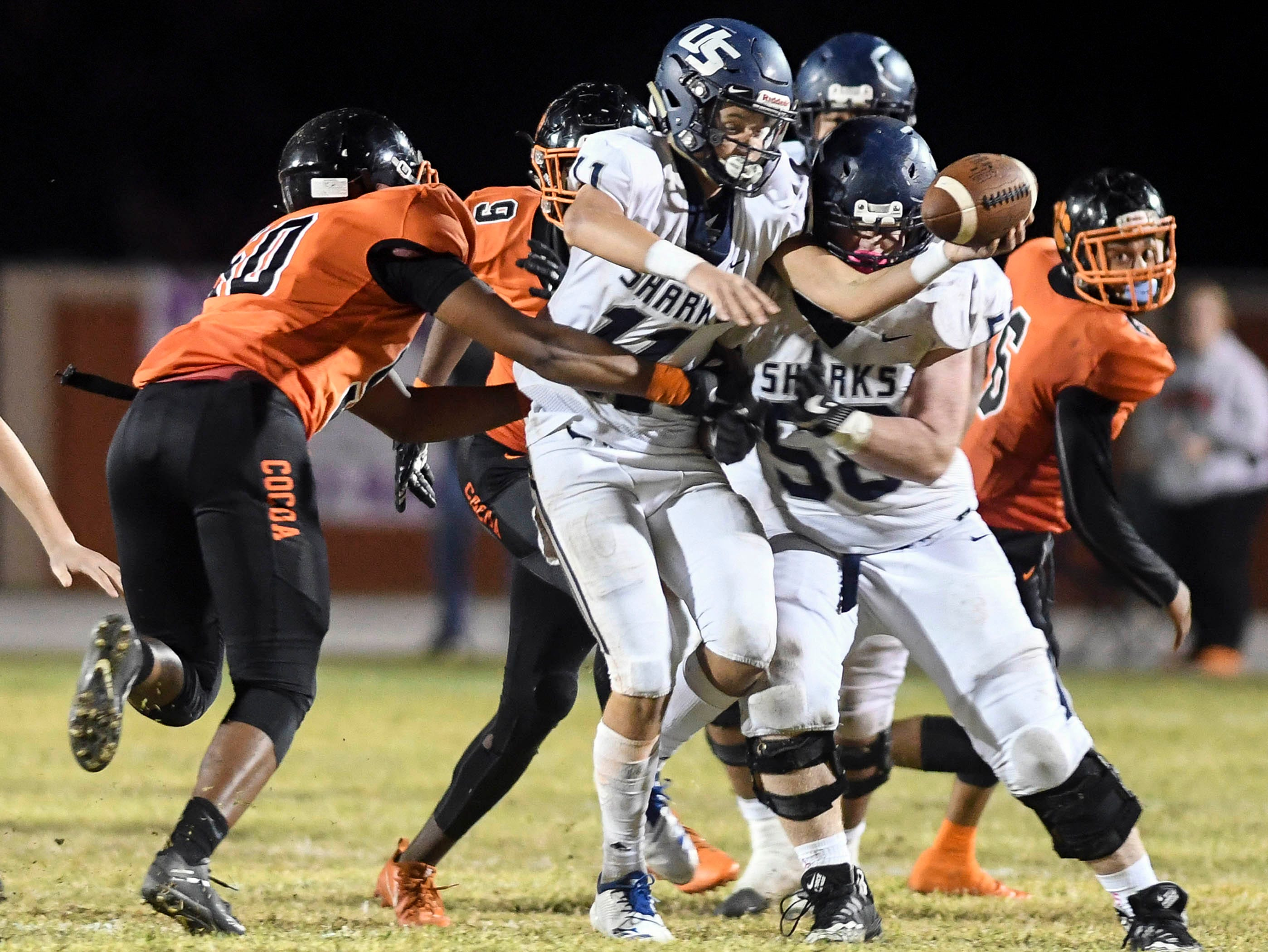 Cocoa players bring down University QB Nick Vattiato during Friday's Class 4A state semifinal.