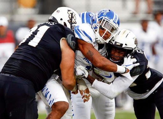 UCF Knights defensive lineman Joey Connors (91) and  defensive back Rashard Causey (21)combine to stop Memphis Tigers wide receiver Tony Pollard (1) during the first quarter at Spectrum Stadium.