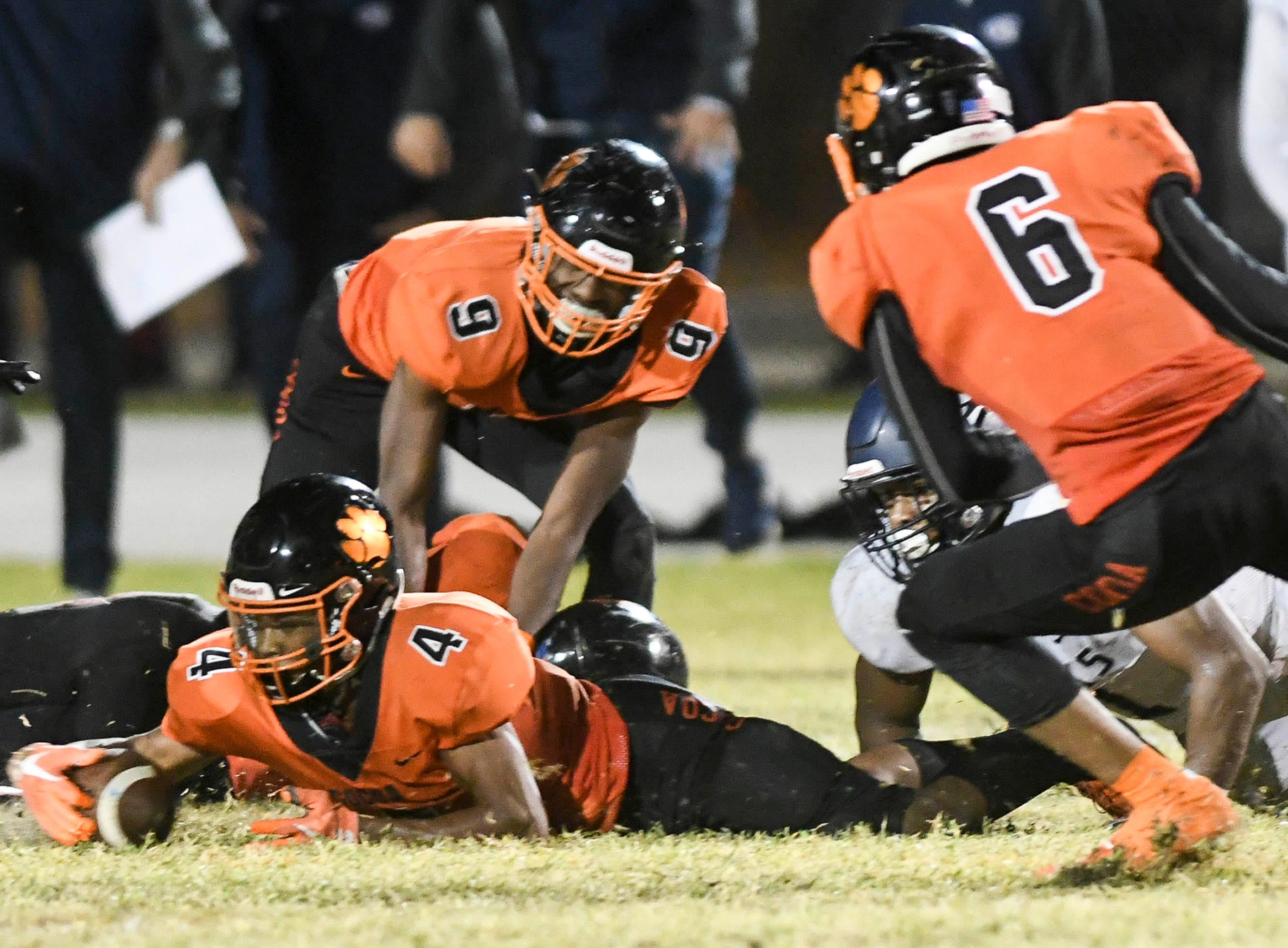 Cocoa's WIllie Gaines (4) recovers a fumble by  University preserving the Tigers 32-31 victory in Friday's Class 4A state semifinal.
