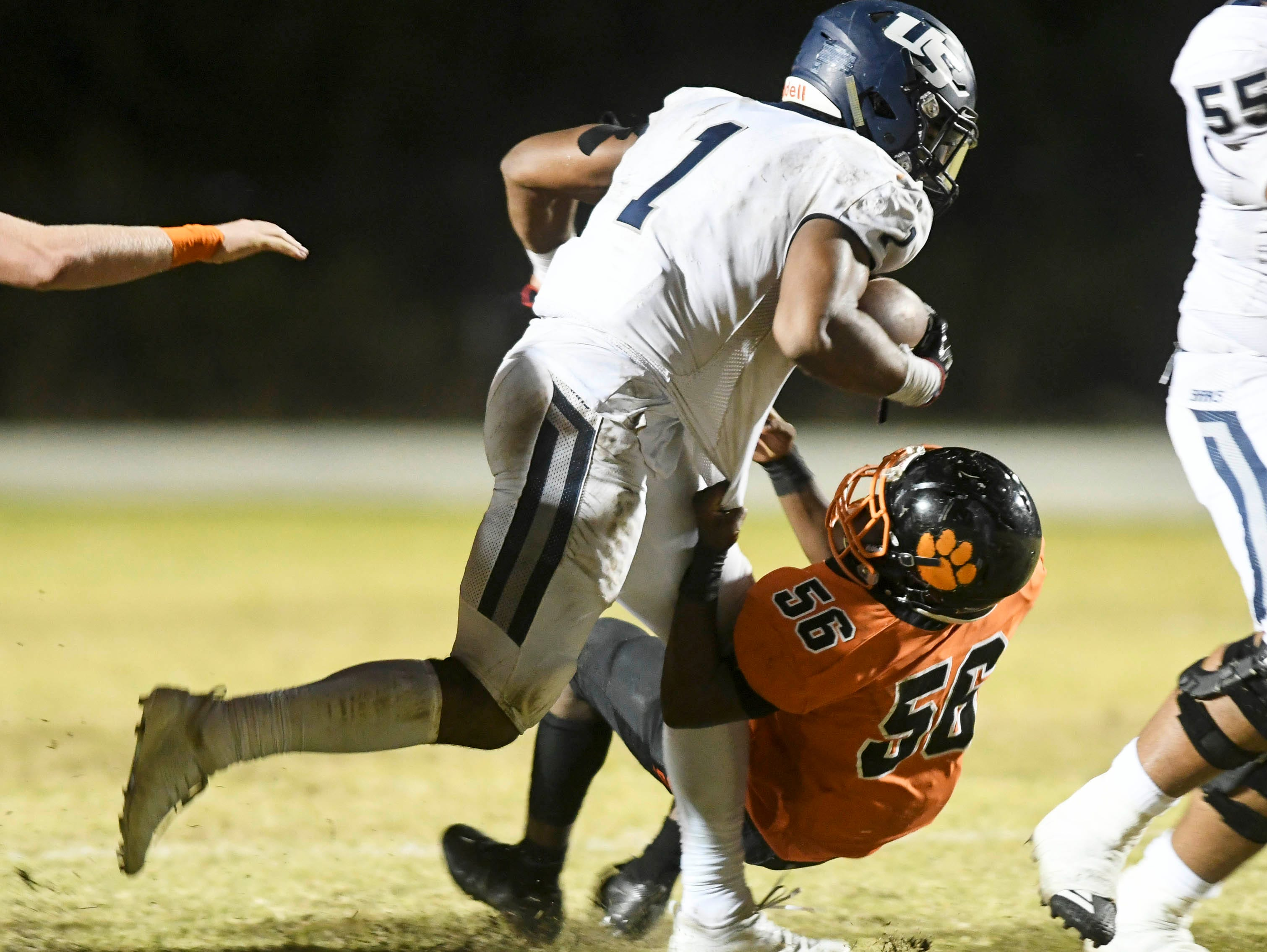 AJ Williams of Cocoa brings down University ballcarrier Kenny Mcintosh during Friday's Class 4A state semifinal.