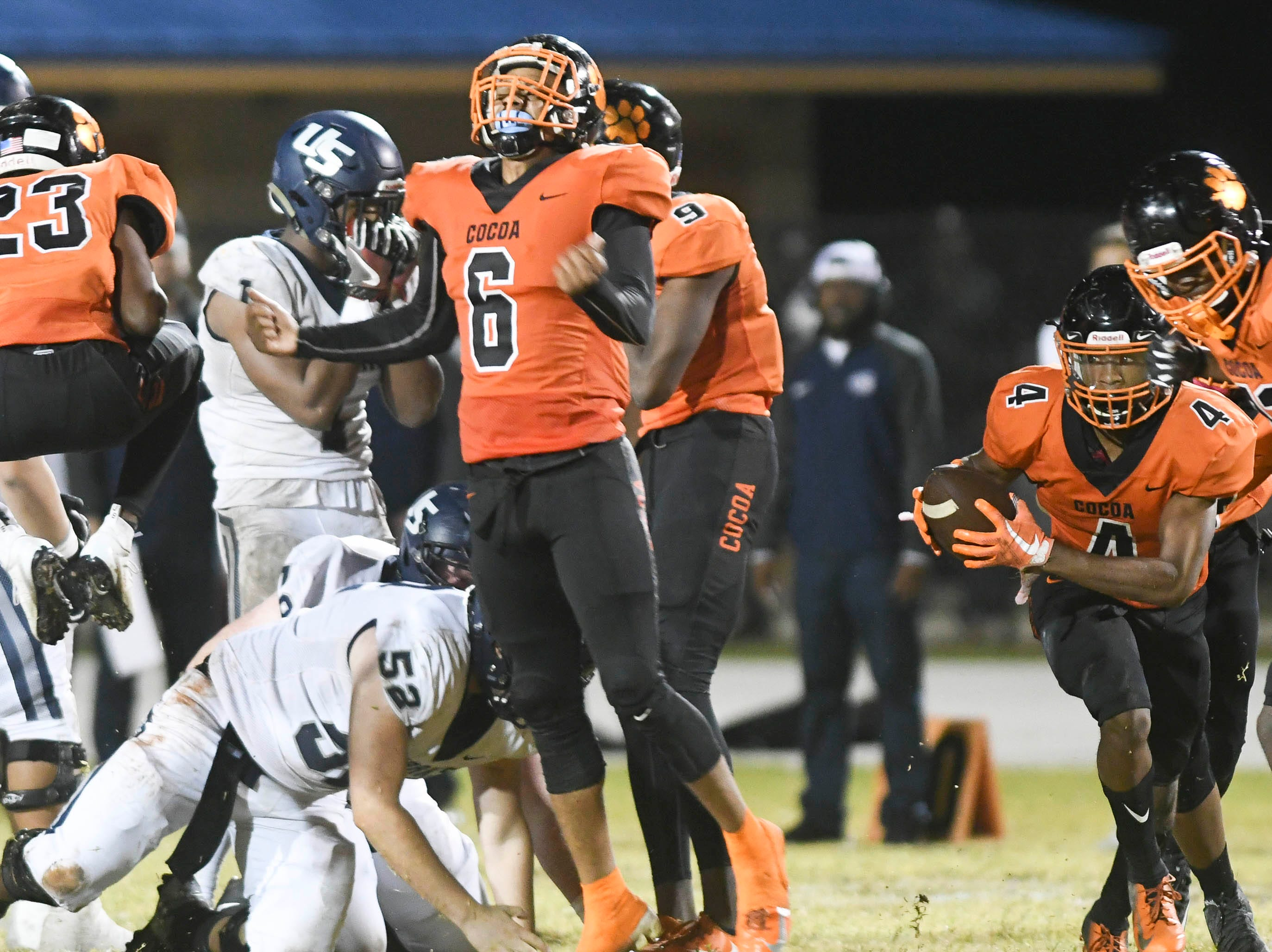 Cocoa's WIllie Gaines (4) recovers a fumble by Kenny Mcintosh of University (1) preserving the Tigers 32-31 victory in Friday's Class 4A state semifinal.