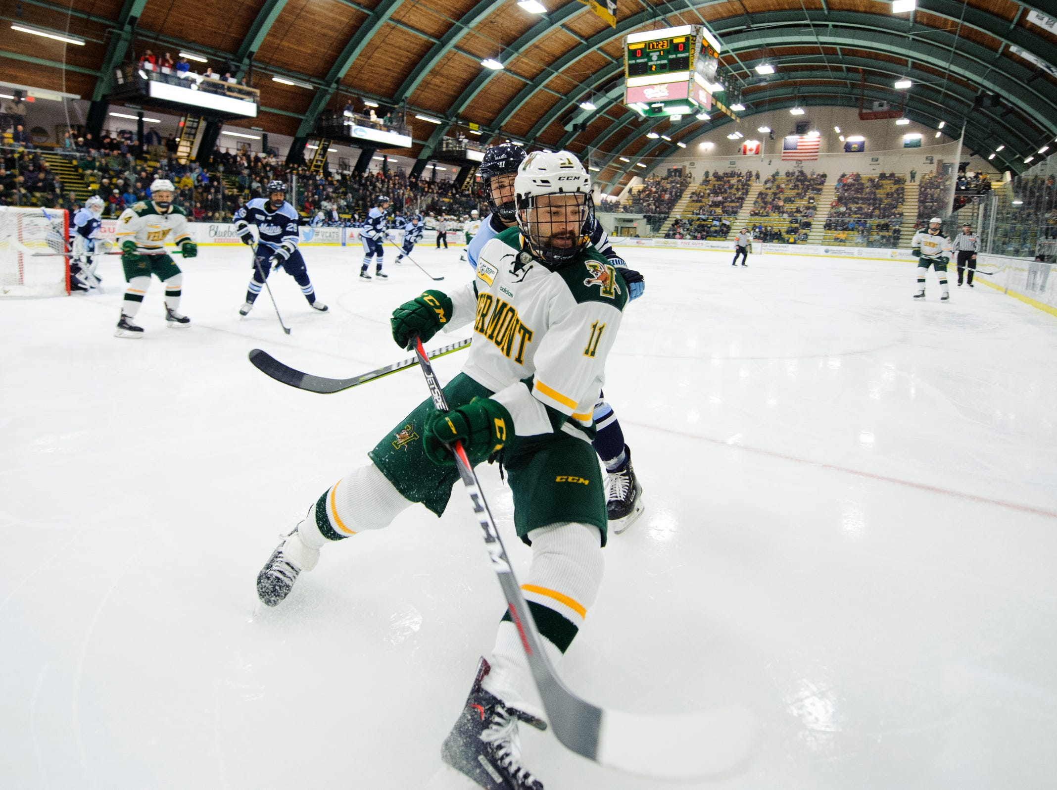 Vermont forward Conor O'Neil (11) battles for the puck in the corner during the men's hockey game between the Mine Black Bears and the Vermont Catamounts at Gutterson Field House on Friday night November 30, 2018 in Burlington.