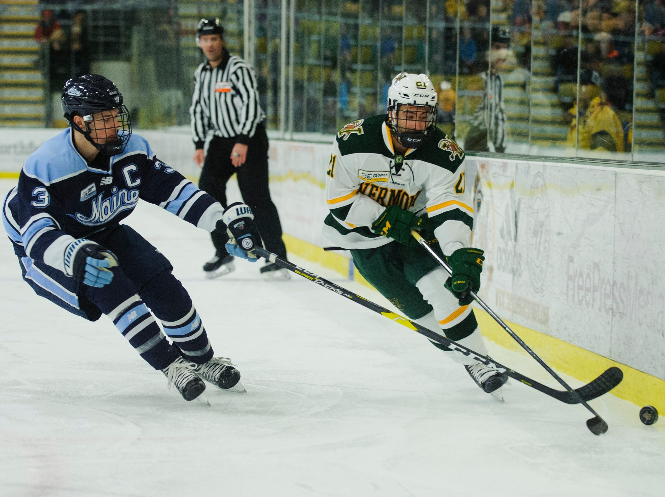 Vermont forward Martin Frechette (21) skates past Maine's Rob Michel (3) during the men's hockey game between the Mine Black Bears and the Vermont Catamounts at Gutterson Field House on Friday night November 30, 2018 in Burlington.