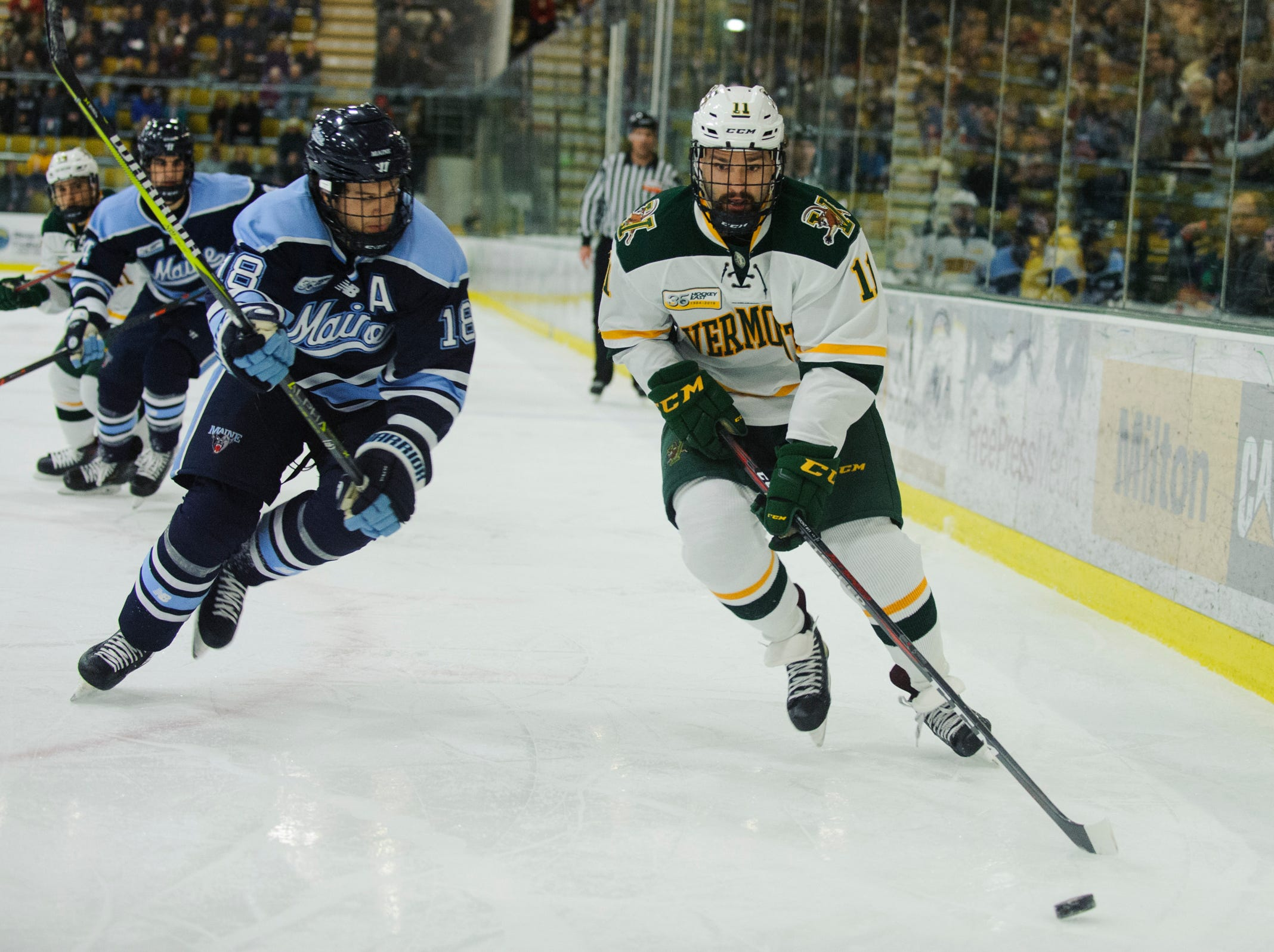 Vermont forward Conor O'Neil (11) skates past Maine's Keith Muehlbauer (18) during the men's hockey game between the Mine Black Bears and the Vermont Catamounts at Gutterson Field House on Friday night November 30, 2018 in Burlington.