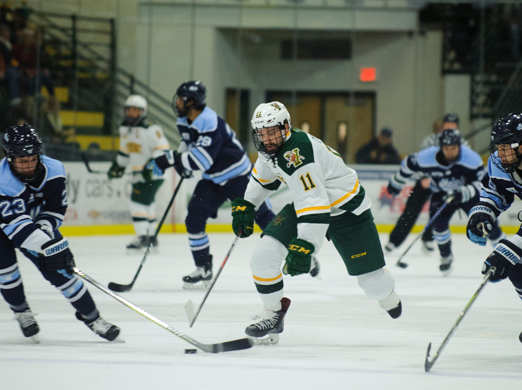 Vermont forward Conor O'Neil (11) battles for the puck during the men's hockey game between the Mine Black Bears and the Vermont Catamounts at Gutterson Field House on Friday night November 30, 2018 in Burlington.