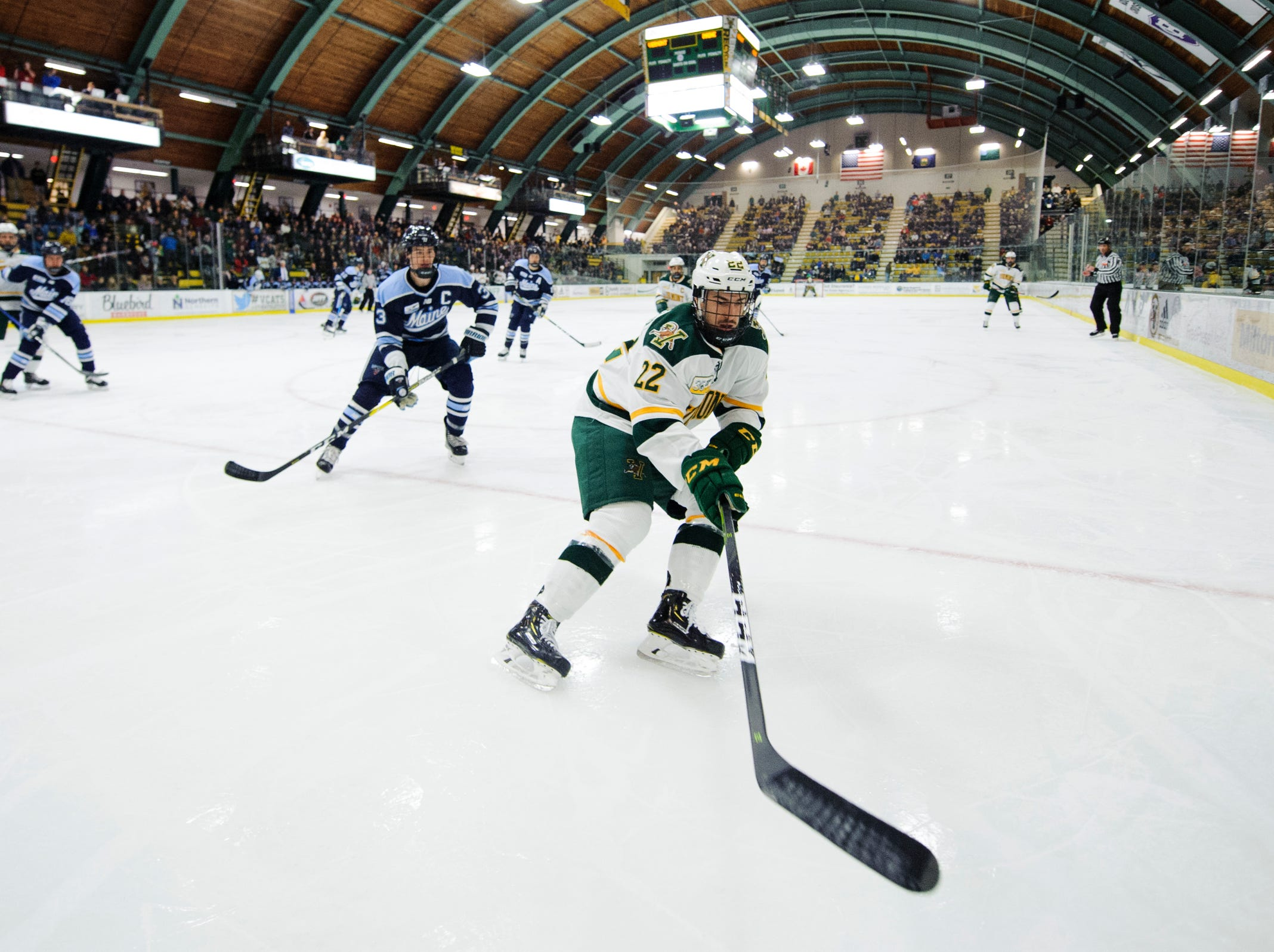 Vermont forward Alex Esposito (22) plays the puck in the corner during the men's hockey game between the Mine Black Bears and the Vermont Catamounts at Gutterson Field House on Friday night November 30, 2018 in Burlington.