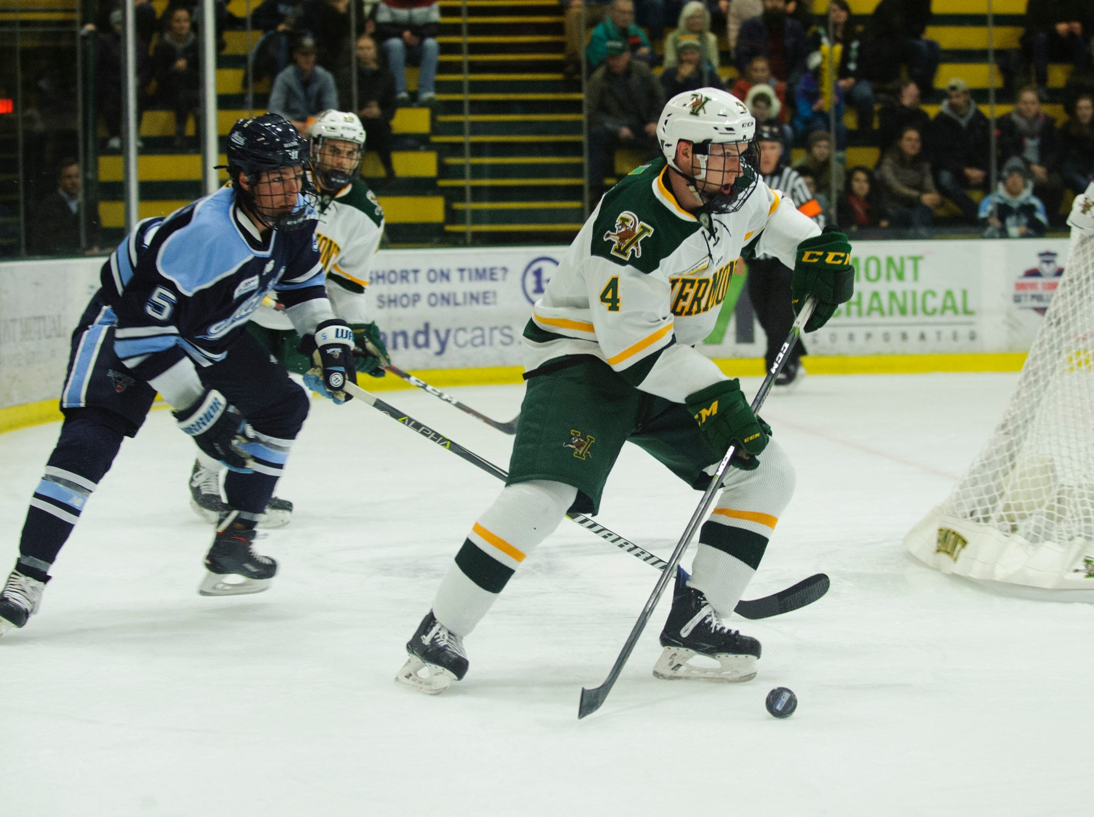 Vermont defenseman Owen Grant (4) looks to pass the puck during the men's hockey game between the Mine Black Bears and the Vermont Catamounts at Gutterson Field House on Friday night November 30, 2018 in Burlington.