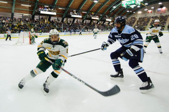 Vermont defenseman Corey Moriarty (15) battles for the puck during the men's hockey game between the Mine Black Bears and the Vermont Catamounts at Gutterson Field House on Friday night November 30, 2018 in Burlington.
