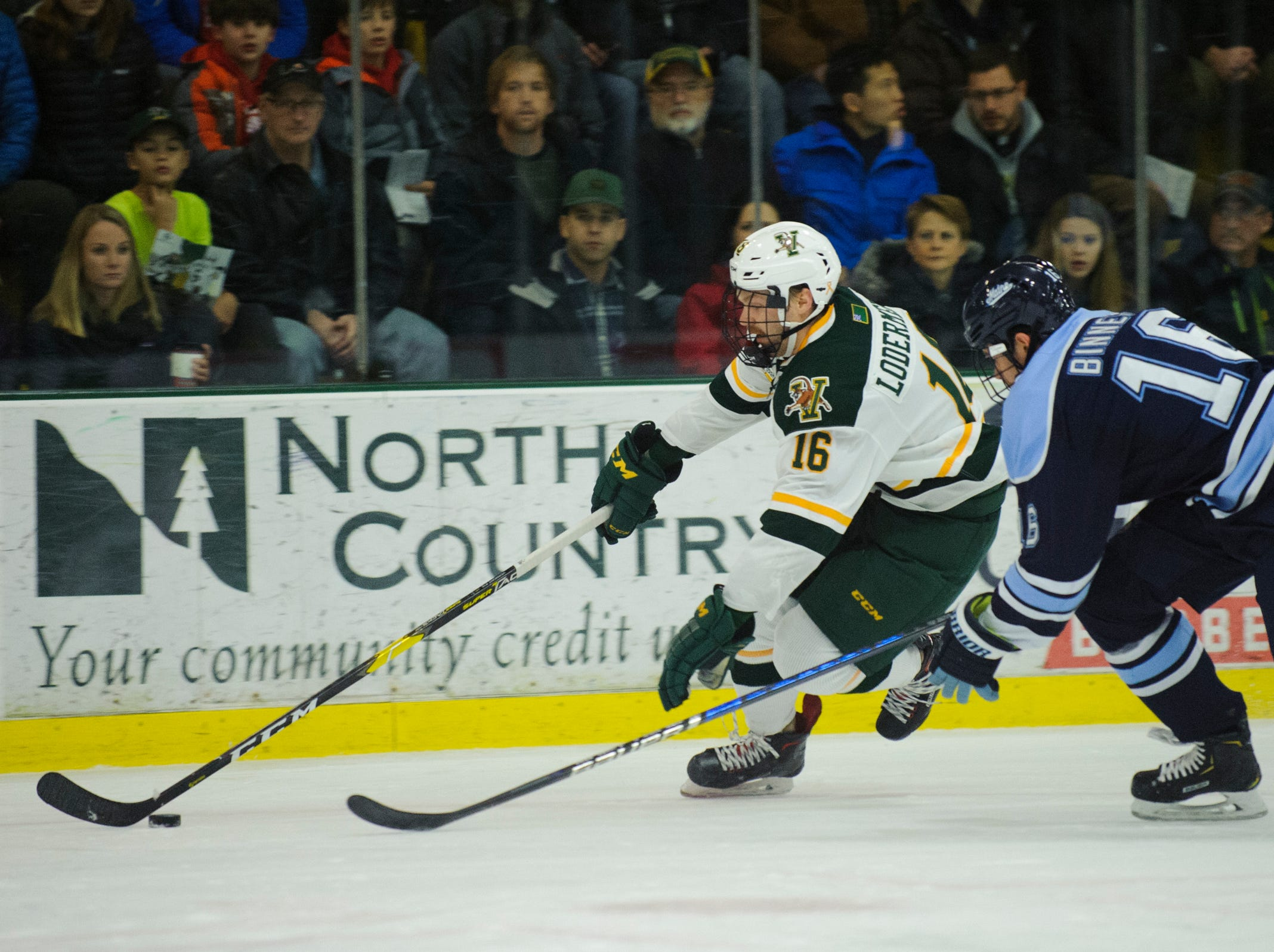 Vermont forward Derek Lodermeier (16) skates with the puck past Maine's Alexis Binner (16) during the men's hockey game between the Mine Black Bears and the Vermont Catamounts at Gutterson Field House on Friday night November 30, 2018 in Burlington.