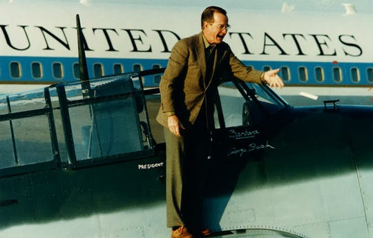 "Vice President/President-elect George H.W. Bush tosses a marker after naming the plane ""Barbara"" and signing his name underneath. The plane had been shipped to NAS-Chase Field by owner Bob Schneider."