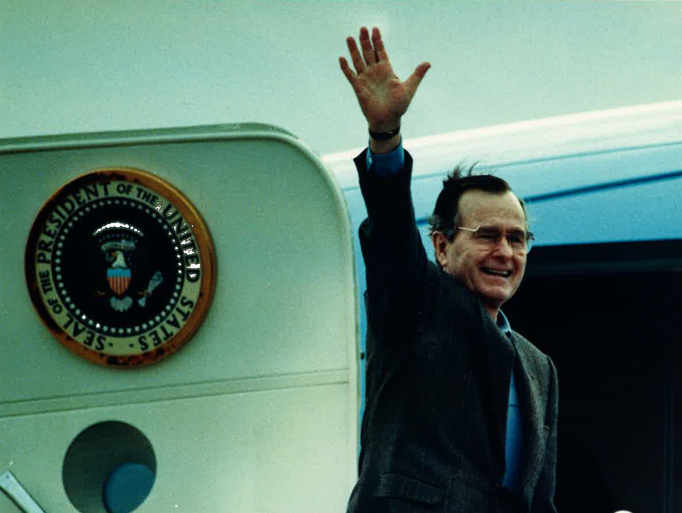 President George H.W. Bush waves to the crowd at NAS-Chase Field before departing for Houston on Air Force One. Bush had been quail hunting and fishing in the area in December 1989.