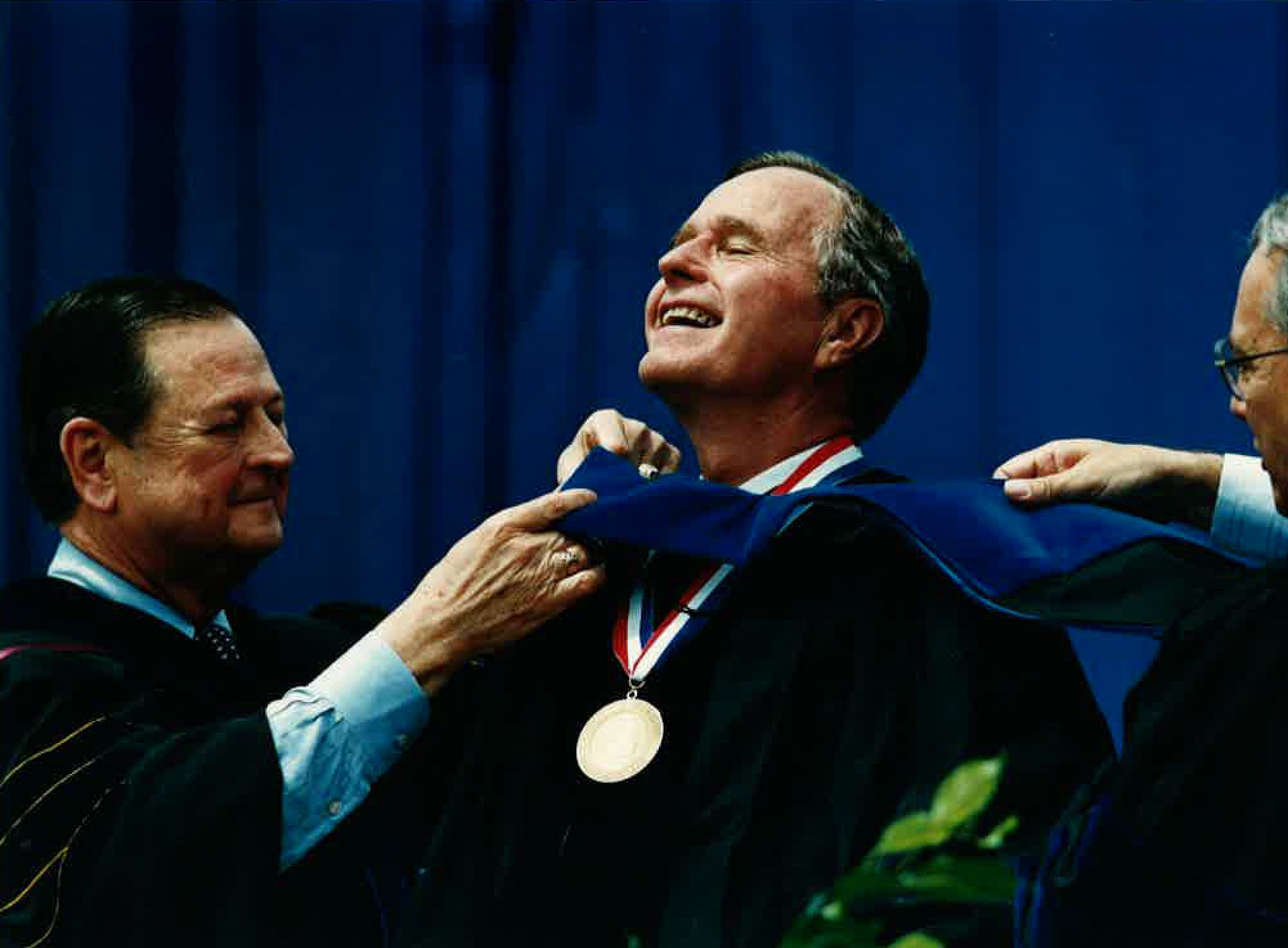 Chairman of the Texas A&M System Board of Regents, William A. McKenzie (eft), and Texas A&I University President Dr. Manuel L. Ibanez present President George H.W. Bush with a doctoral hood after presenting him an honorary degree medal prior to Bush's commencement address in May 1990.