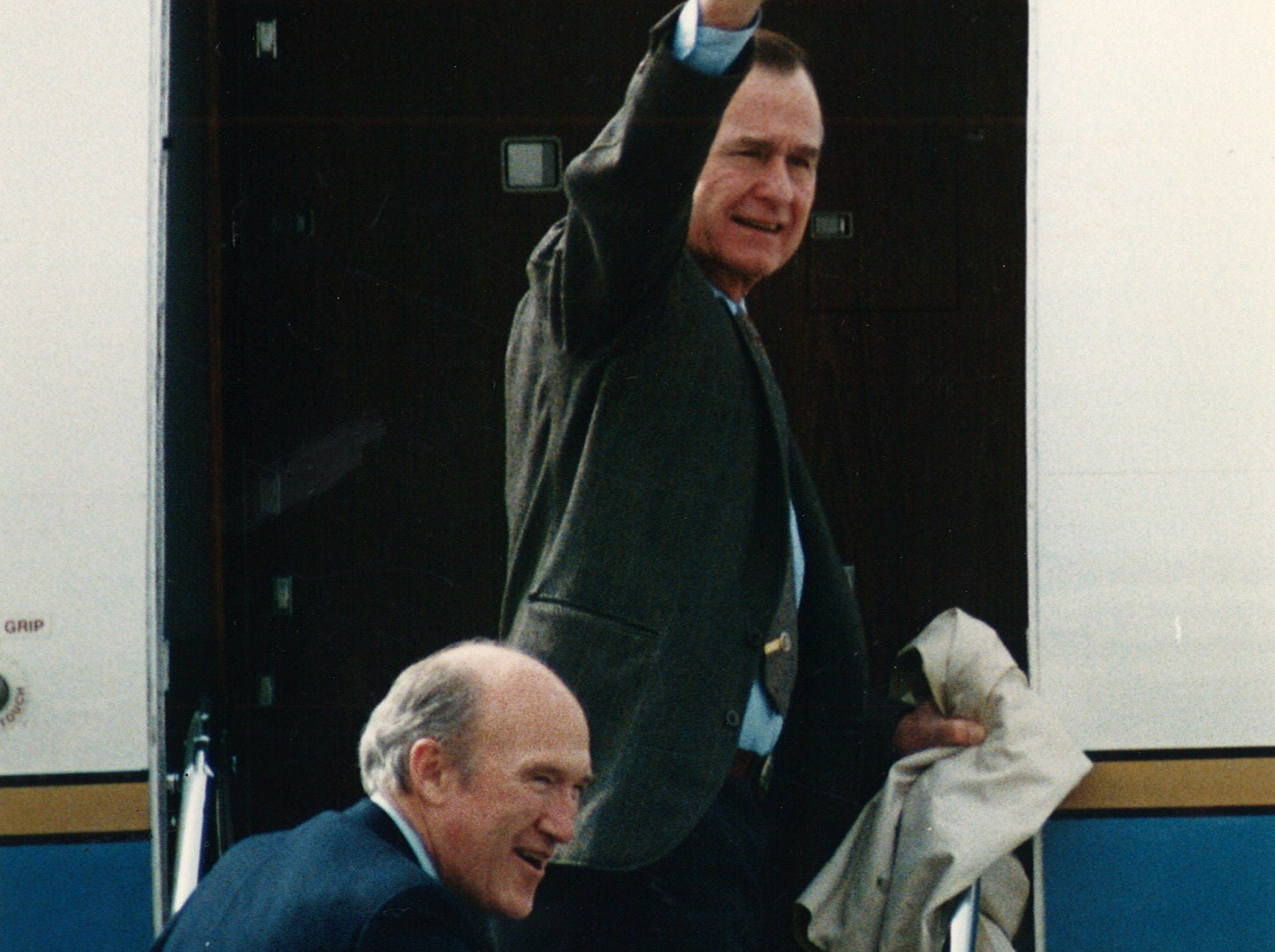 U.S. President George Bush aves to a handful of well-wishers as he and U.S. Senator Alan Simpson board their plane and leave Naval Air Station Chase Field in Beeville, Texas in December 1991.