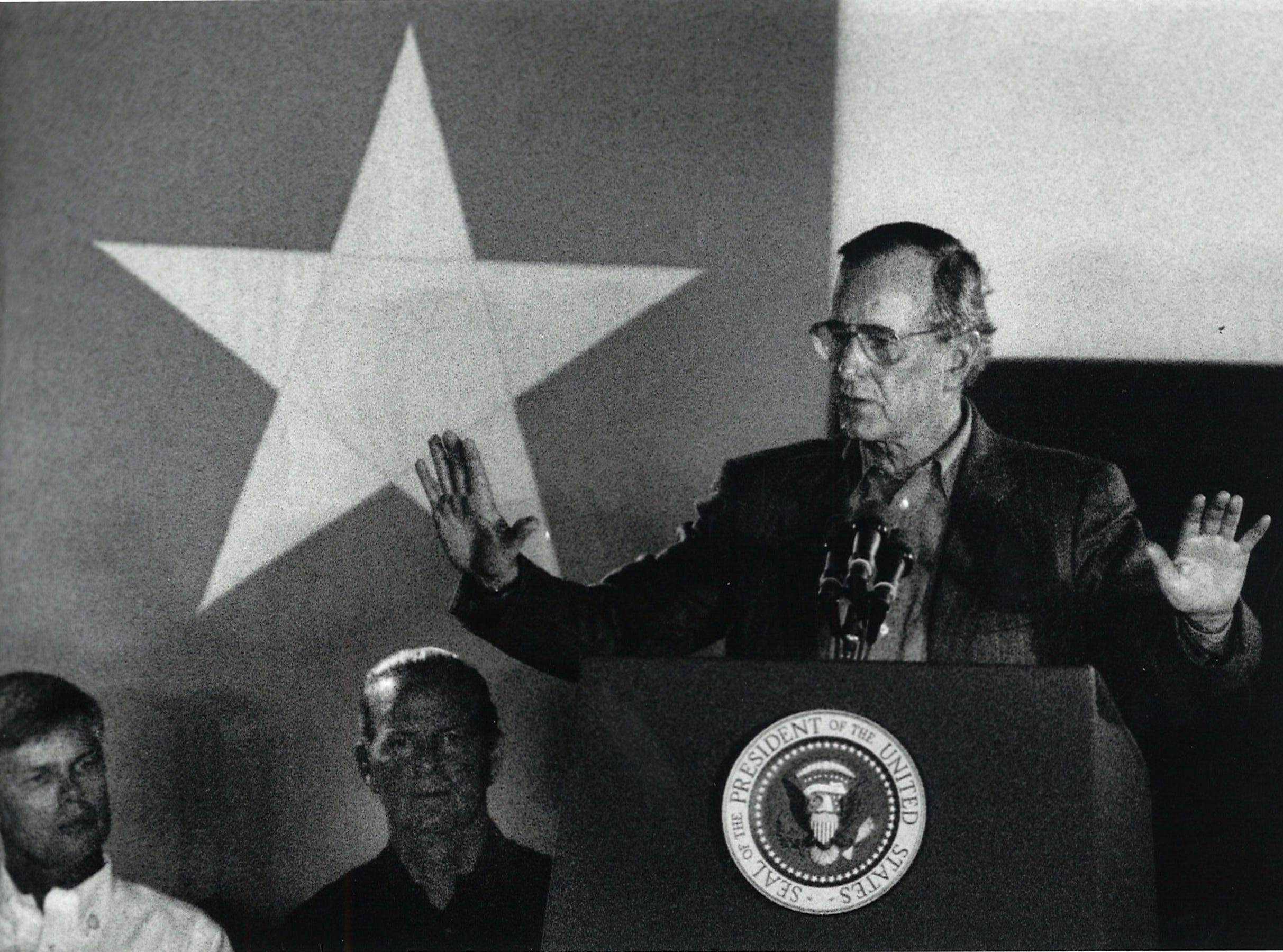 President George Bush addresses the crowd inside the Bee County Coliseum on Dec. 30, 1989, during the Presidential Appreciation Barbecue prior to his hunting trip in Berclair. Behind him are Jay Kimbrough, Beeville Bush Appreciation dinner co-organizer, left, and Secretary of State James Baker.