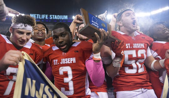 St. Joseph's Jada Byers holds the NJSIAA Non-Public 2 state championship trophy after a 41-22 win over Holy Spirit at MetLife Stadium on Friday, November 30, 2018.