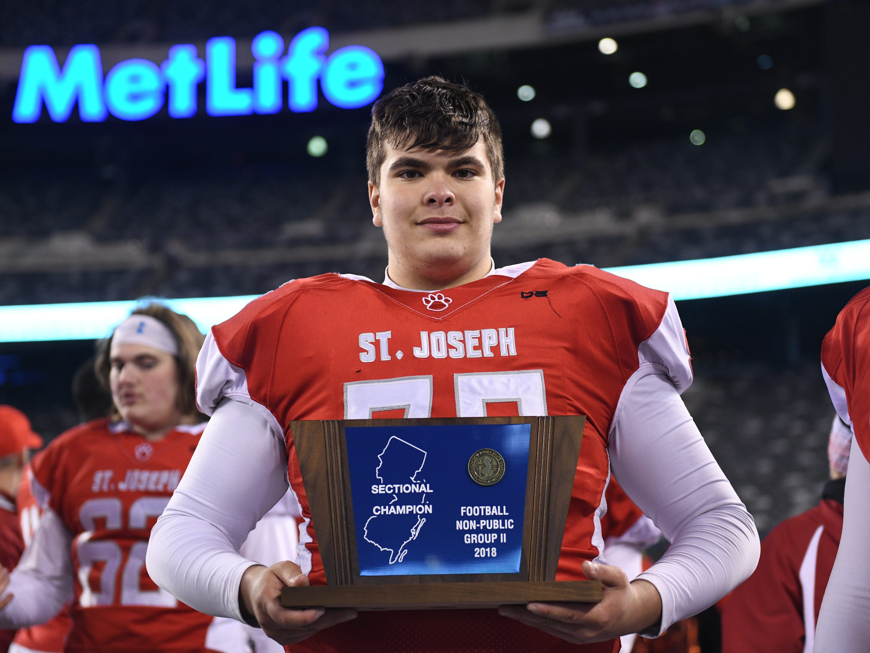St. Joseph's Dominic Midure holds the Non-Public 2 state championship trophy after the Wildcats topped the Spartans, 41-22 at MetLife Stadium on Friday, November 30, 2018.