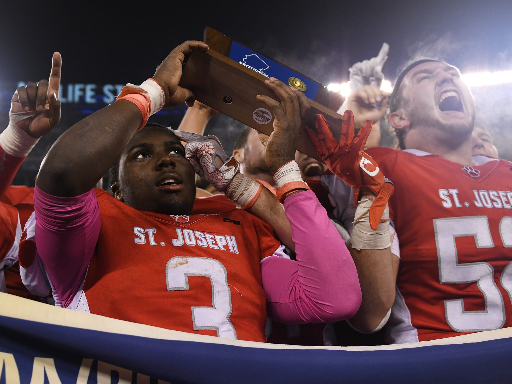 St. Joseph's Jada Byers raises the NJSIAA Non-Public 2 state championship trophy after a 41-22 win over Holy Spirit at MetLife Stadium on Friday, November 30, 2018.