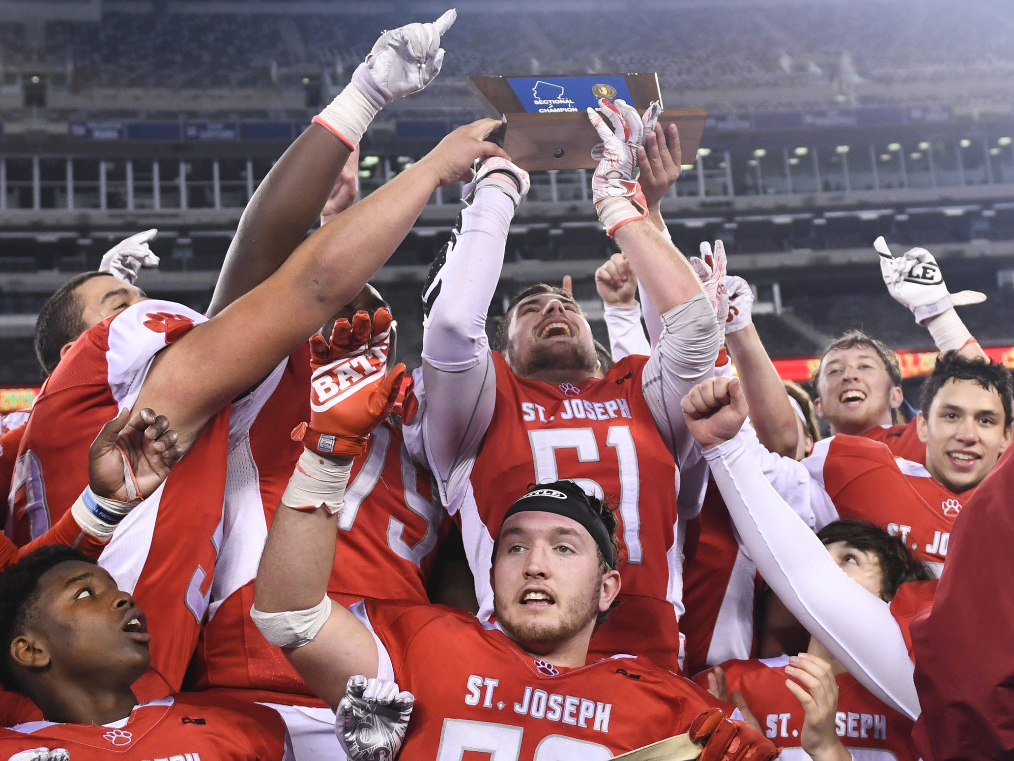 St. Joseph's Bobby Hyndman raises the NJSIAA Non-Public 2 state championship trophy after a 41-22 win over Holy Spirit at MetLife Stadium on Friday, November 30, 2018.
