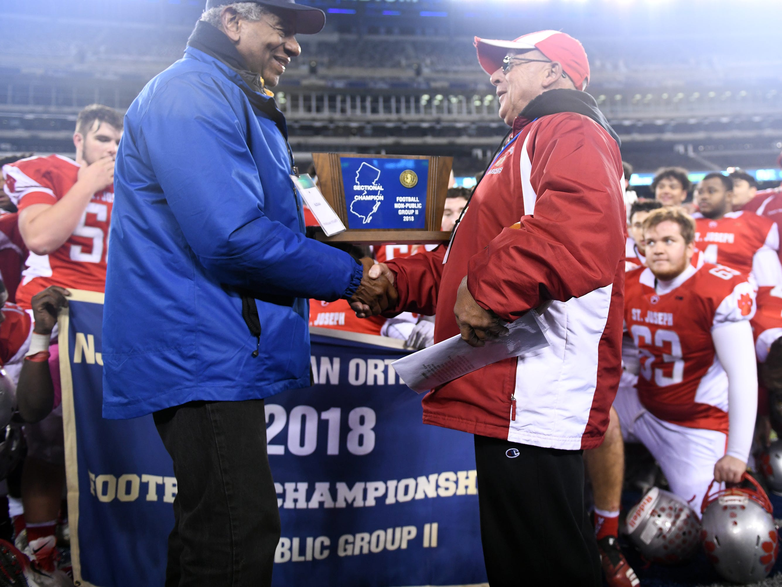 St. Joseph coach Paul Sacco Jr. (right) accepts the Non-Public 2 state championship trophy after beating Holy Spirit at MetLife Stadium on Friday, November 30, 2018.