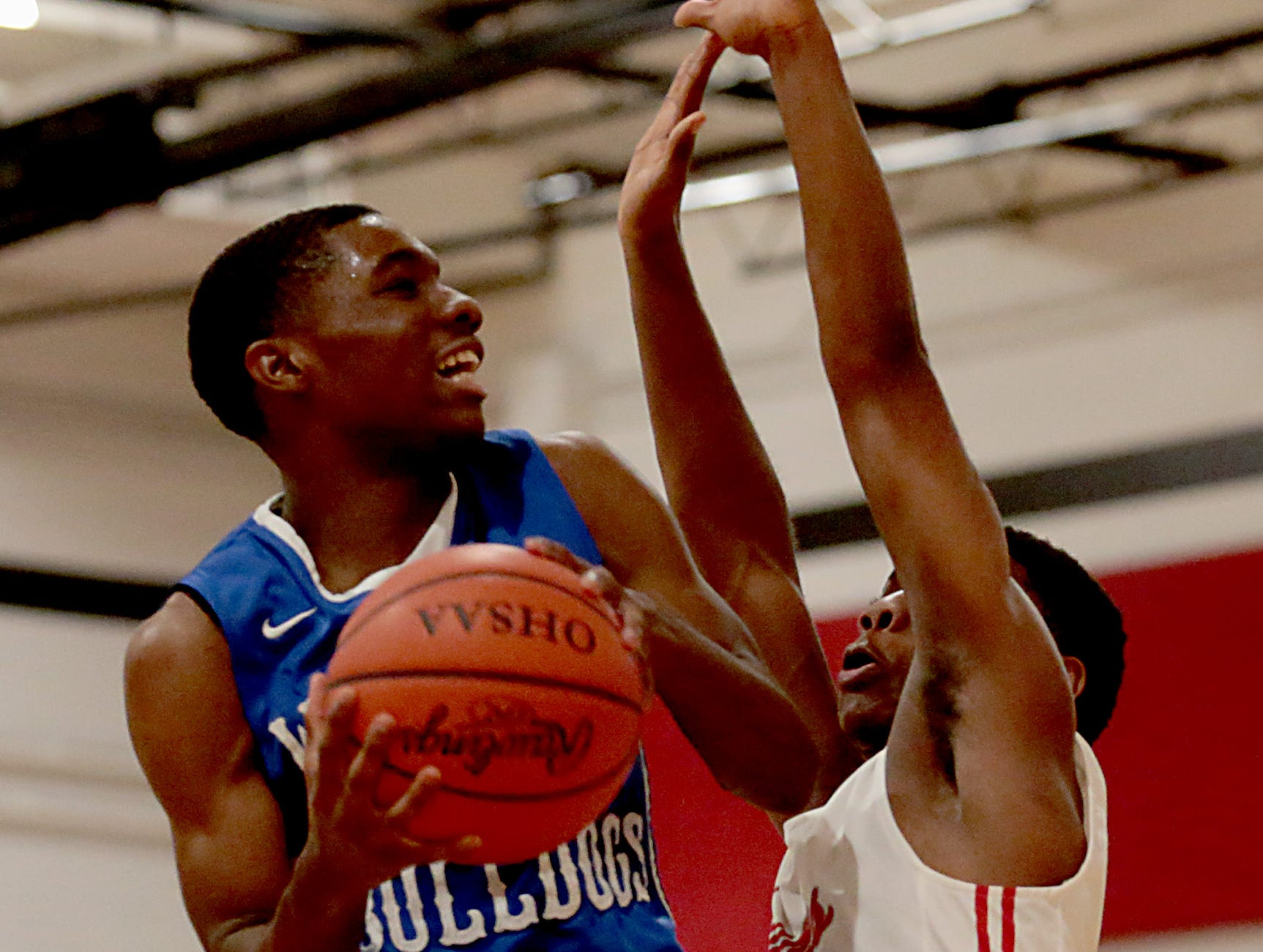 Woodward guard Marquez Whitmire shoots against Hughes guard Keontay Wills during their game at Hughes in Clifton Friday, Nov. 30, 2018.