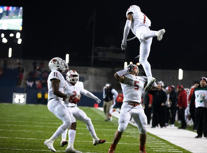 Colerain's Syncere Jones (1) is tossed in the air by Ivan Pace Jr. (5) after scoring a touchdown during the first half of the OHSAA Div. I State Championship football game between St. Edwards and Colerain on Friday, Nov. 30, 2018, at Tom Benson Stadium in Canton.