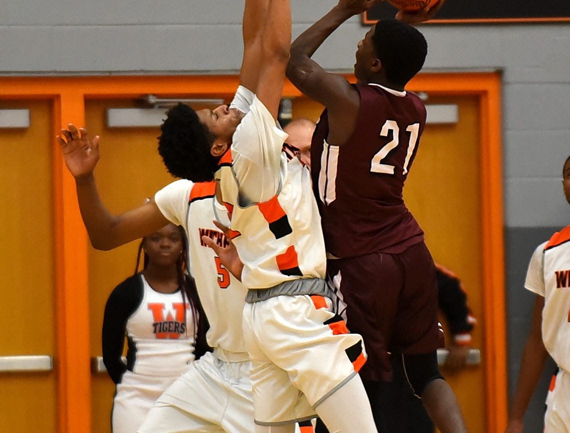 Santais Bell (21) of Western Hills pushes up a shot for the Mustangs over the Withrow defense, November 30, 2018.