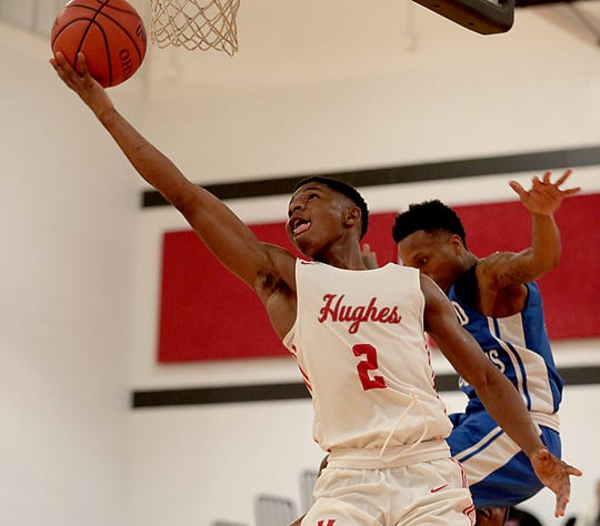 Hughes guard A.B. Harouna shoots in front of Woodward guard Dionte McBride during their game at Hughes in Clifton Friday, Nov. 30, 2018.