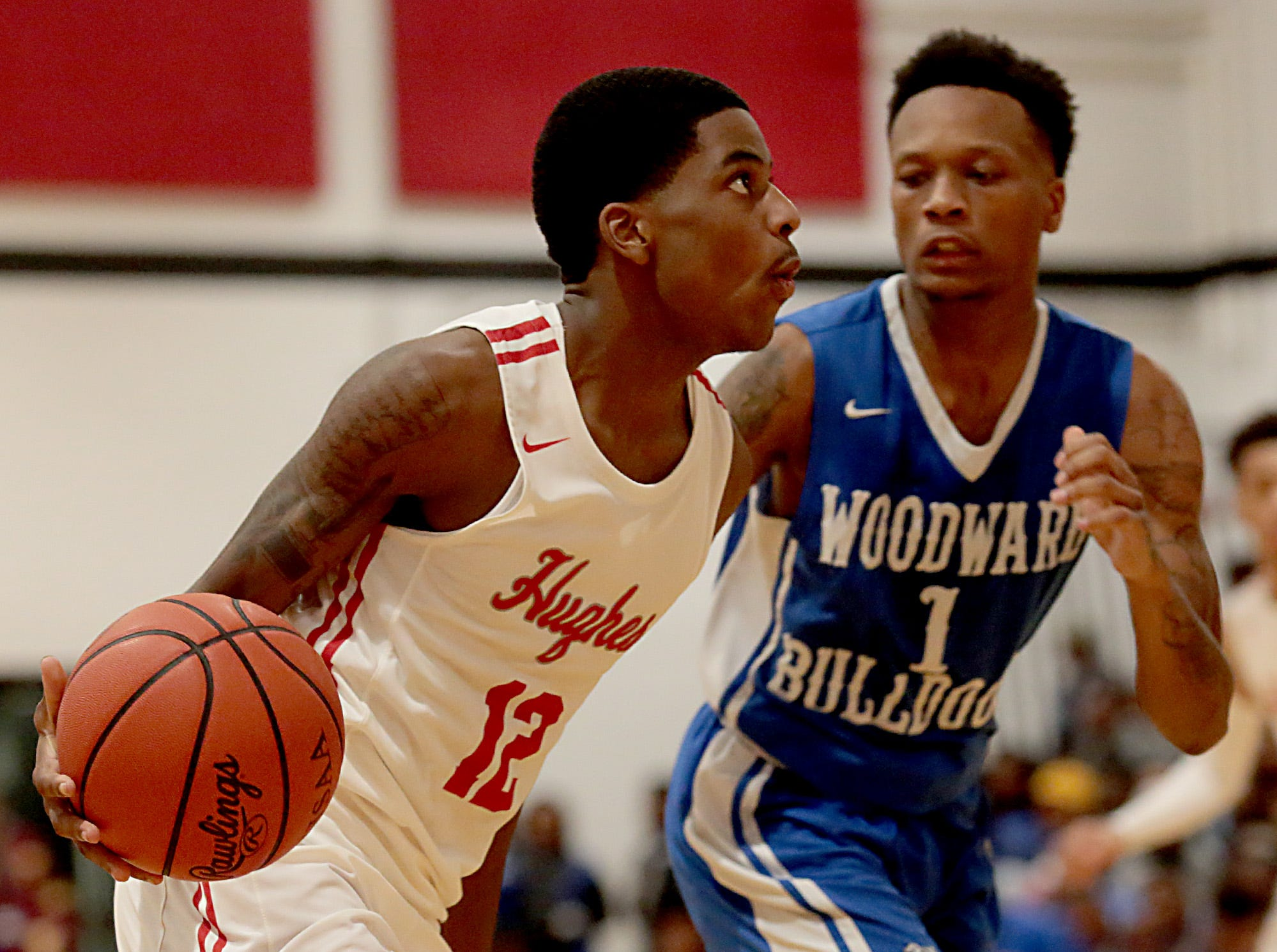 Hughes guard Camron McKenzie drives the lane as Woodward guard Dionte McBride pursues during their game at Hughes in Clifton Friday, Nov. 30, 2018.
