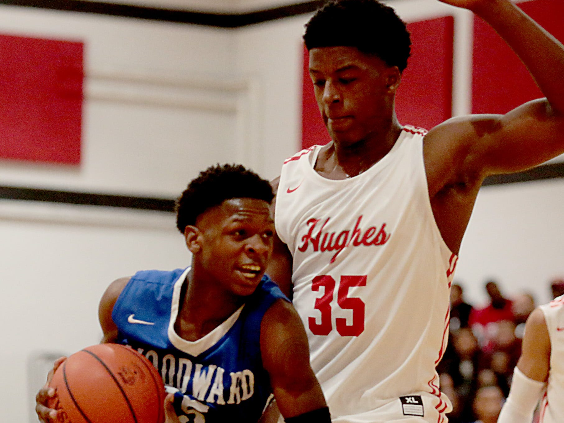 Woodward guard Monte Lewis tries to drive on Hughes center Kenny Jackson during their game at Hughes in Clifton Friday, Nov. 30, 2018.