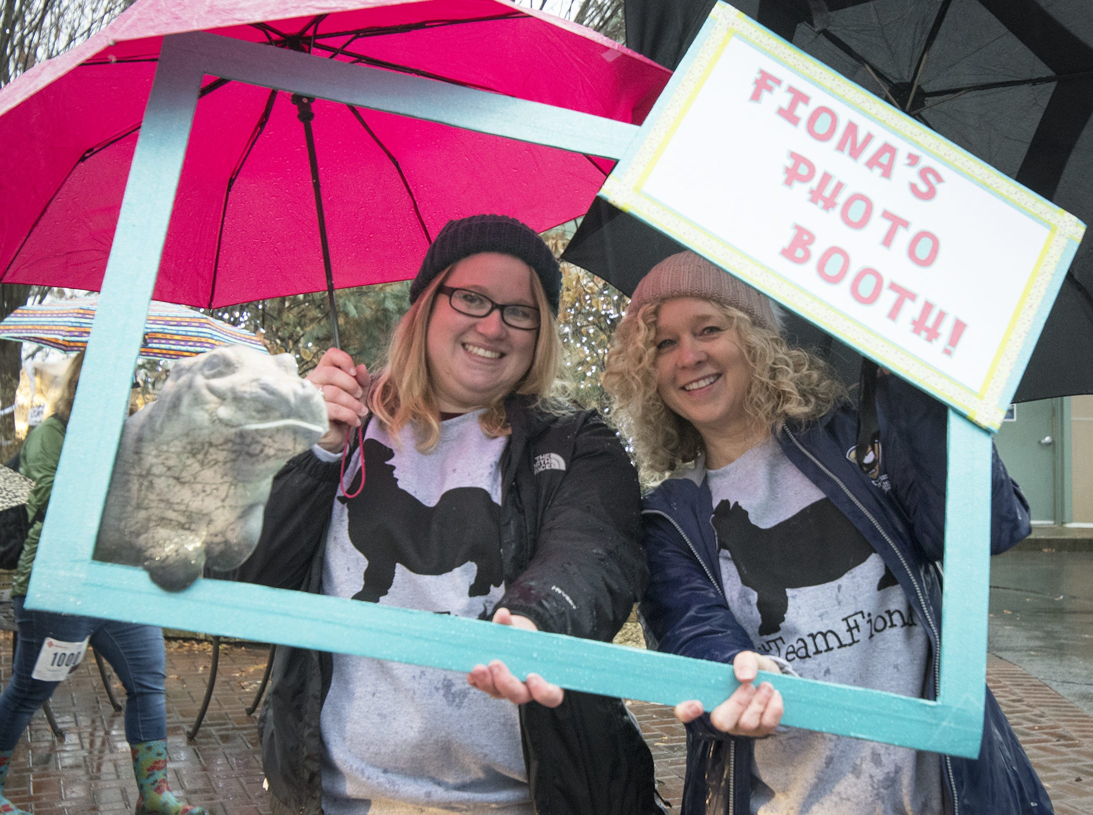 Katie Scott and Jackie Lindner of Milford made a special sign to take photos at the Cincinnati Zoo's Fiona 1k walk in honor of the beloved hippo's 1,000-pound milestone Saturday, December 1, 2018 in Cincinnati, Ohio.