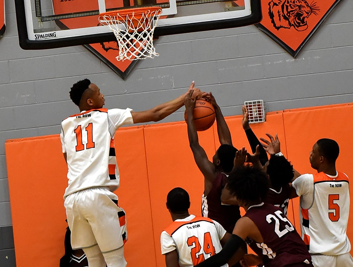 Abba Lawal (11) snuffs out a shot from Western Hills but the Tigers fall to the Mustangs on their home floor, November 30, 2018.
