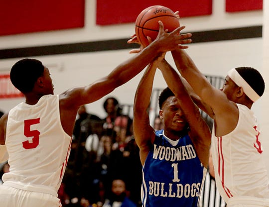 Woodward guard Dionte McBride loses the ball to Hughes guard Kionte Thomas and forward Tyon Thompson during their game at Hughes in Clifton Friday, Nov. 30, 2018.