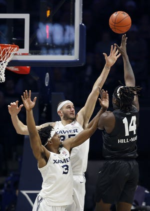 Xavier Musketeers guard Quentin Goodin (3) and forward Zach Hankins (35) guard Oakland Golden Grizzlies forward Xaiver Hill-Mais (14) in the first half of the NCAA basketball game between the Xavier Musketeers and the Oakland Golden Grizzlies at the Cintas Center in Cincinnati on Saturday, Dec. 1, 2018. Xavier led 41-36 at halftime.