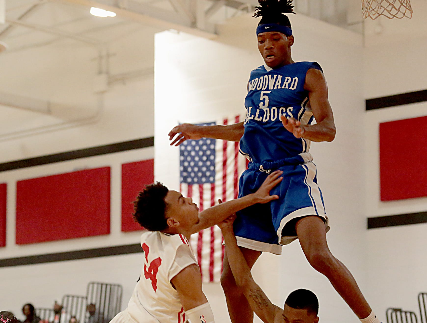 Woodward guard Dre Lewis (10) draws a blocking foul against Hughes guard Paul McMillan during their game at Hughes in Clifton Friday, Nov. 30, 2018. Woodward forward Davion Mace (5) is also in on the play.