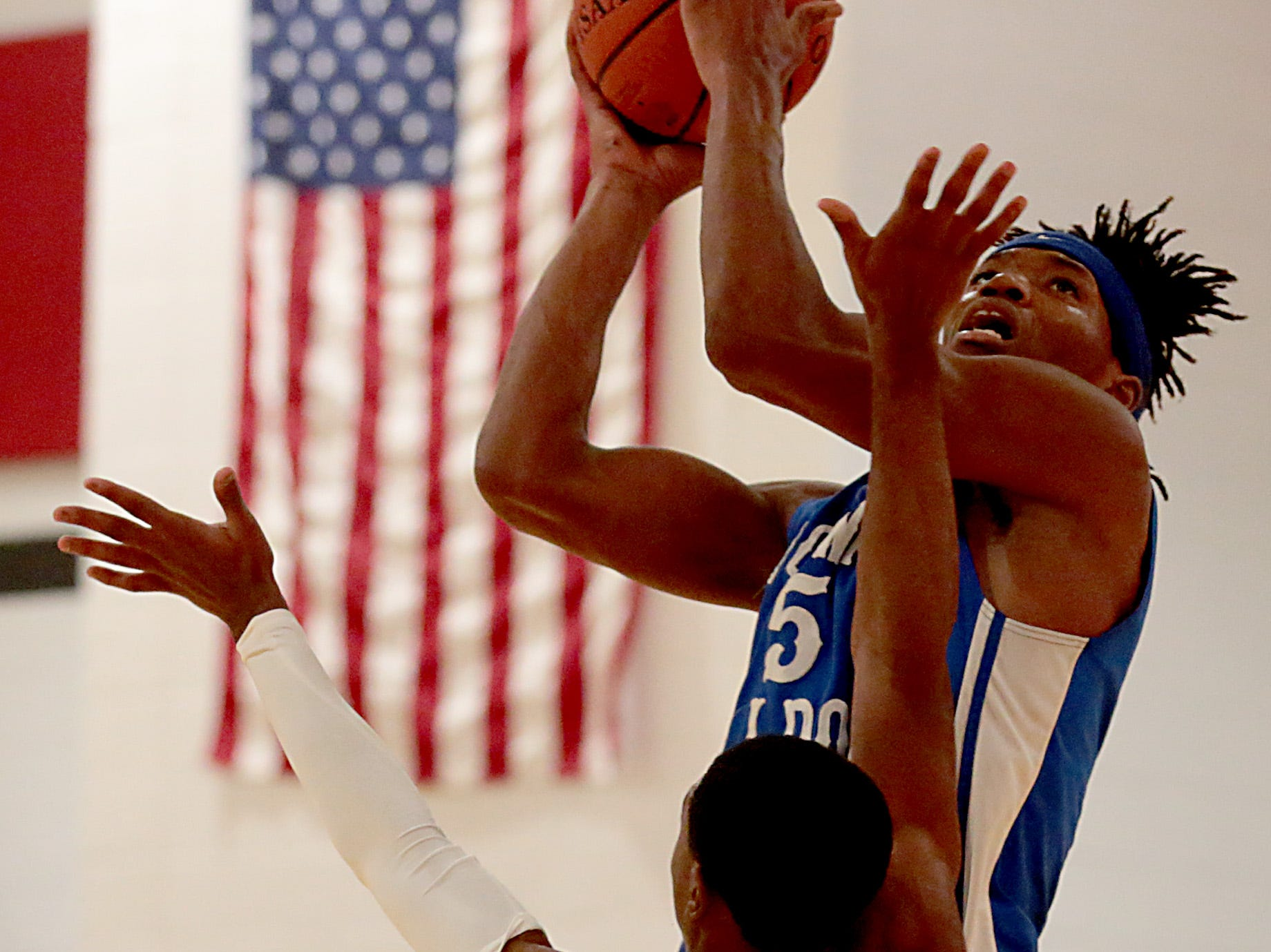 Woodward forward Davion Mace puts a rebound up for two against Hughes guard Kionte Thomas during their game at Hughes in Clifton Friday, Nov. 30, 2018.