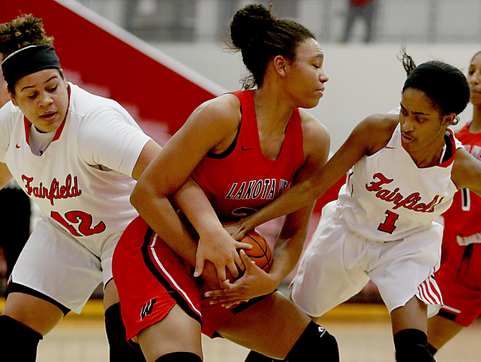 Lakota West's Nevaeh Dean tries to keep the ball from Fairfield's Maddie Schaeffer and Shaniyah Reese during their game at Fairfield Saturday, Dec. 1, 2018.