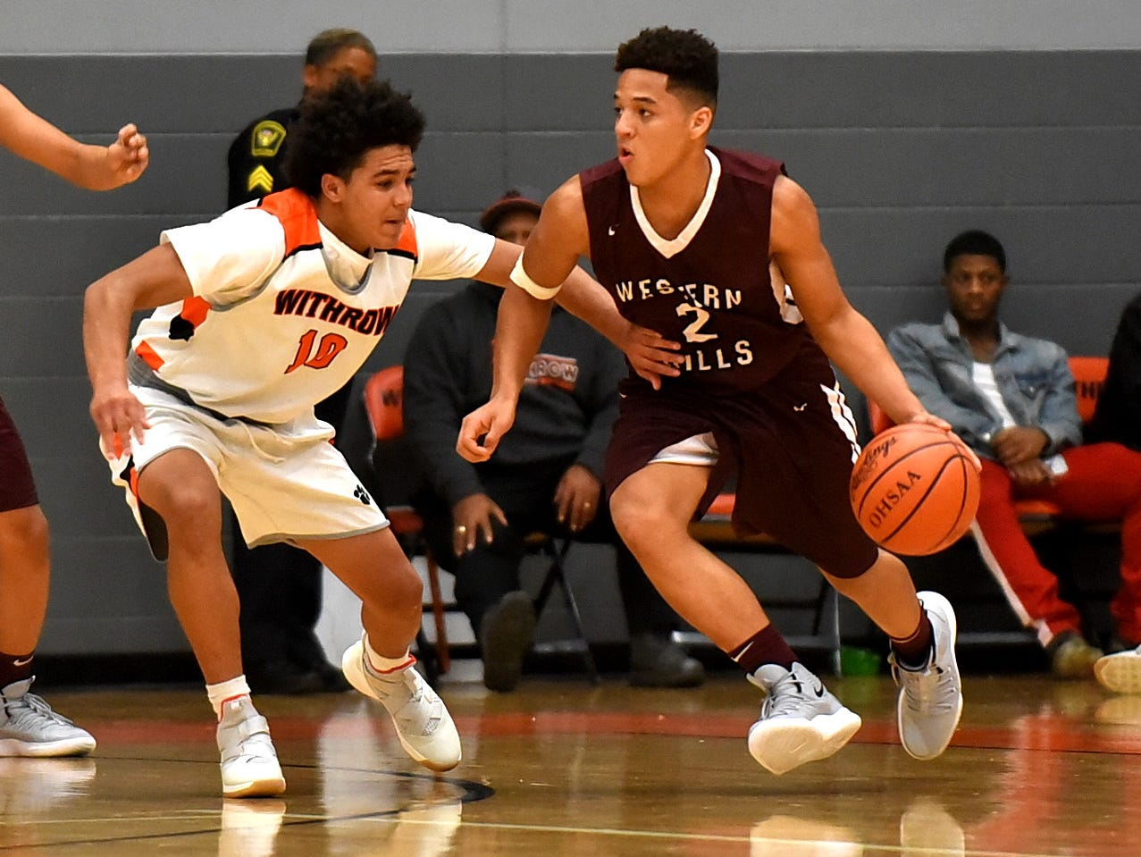 Julian Norman (2) of Western Hills dribbles through the hand check defense of Withrow's Winston Combs (10), Nov. 30, 2018.