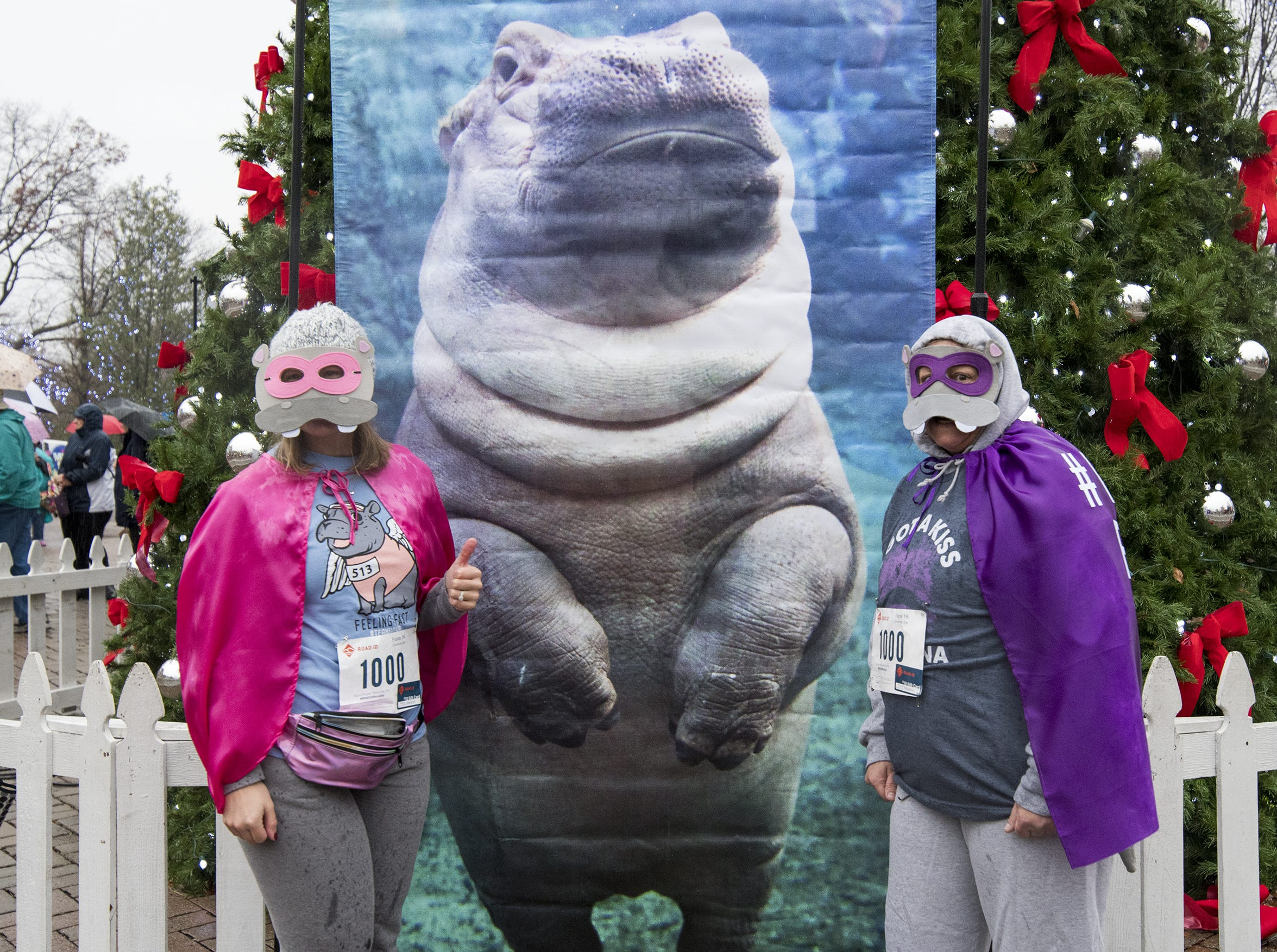 Leigh Hartung of Delhi and Linda Gold of White Oak pose with a giant Fiona poster at the Cincinnati Zoo's Fiona 1k walk in honor of the beloved hippo's 1,000-pound milestone Saturday, December 1, 2018 in Cincinnati, Ohio.