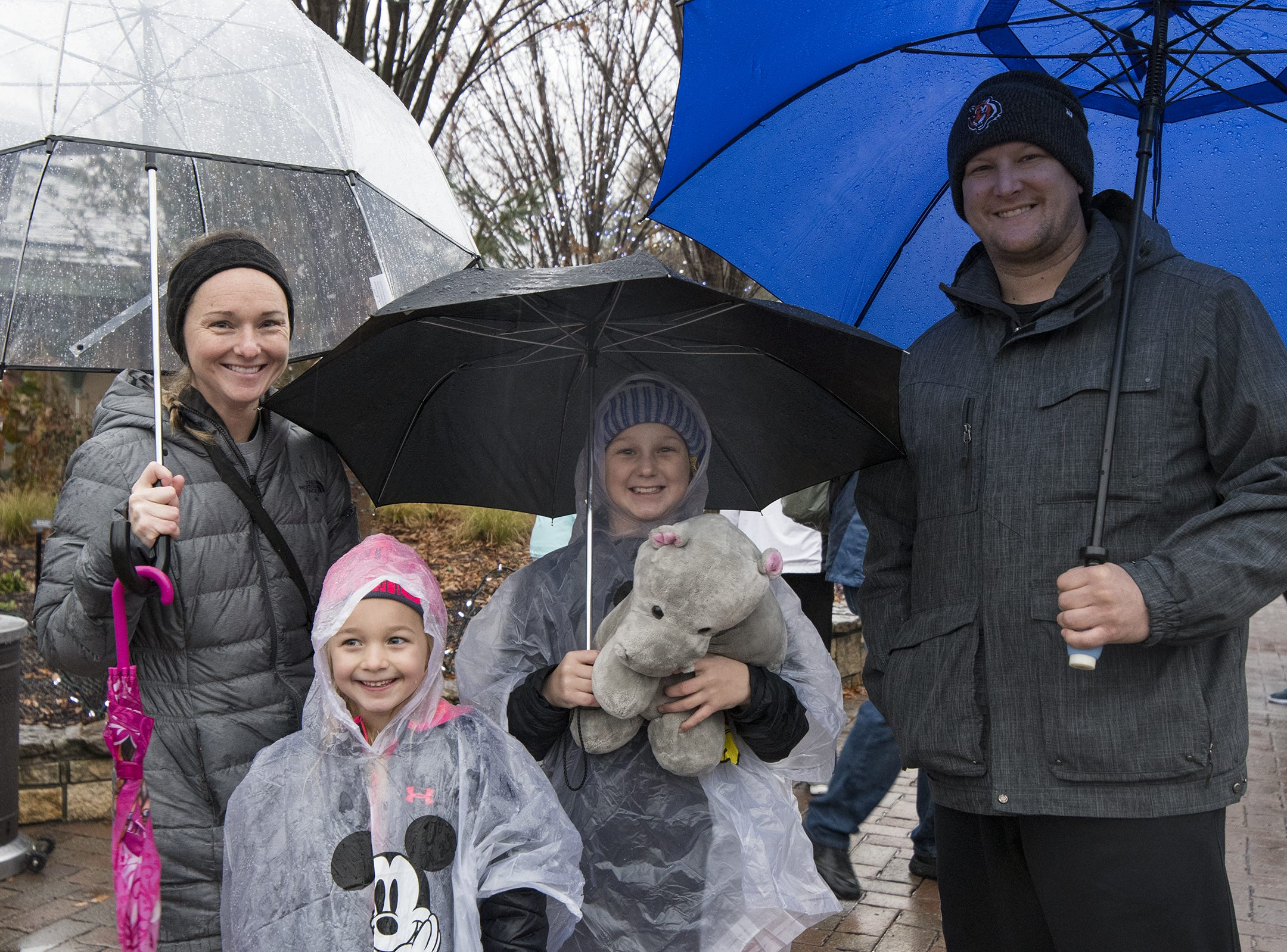 Jessica, Alli, and Paisley Meyers and Dan Hiser try to stay try at the Cincinnati Zoo's Fiona 1k walk in honor of the beloved hippo's 1,000-pound milestone Saturday, December 1, 2018 in Cincinnati, Ohio.