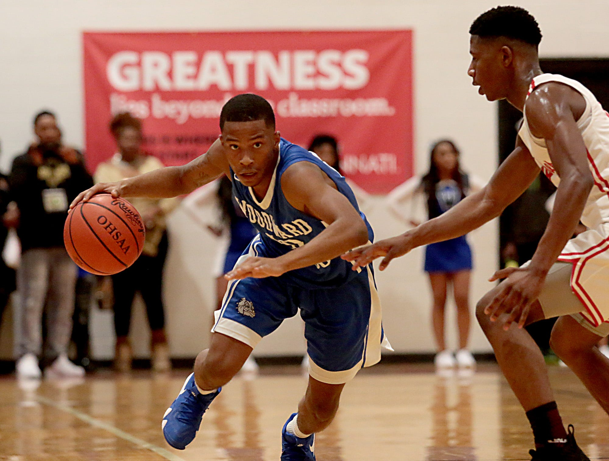 Woodward guard Dre Lewis brings the ball up court against Hughes during their game at Hughes in Clifton Friday, Nov. 30, 2018.