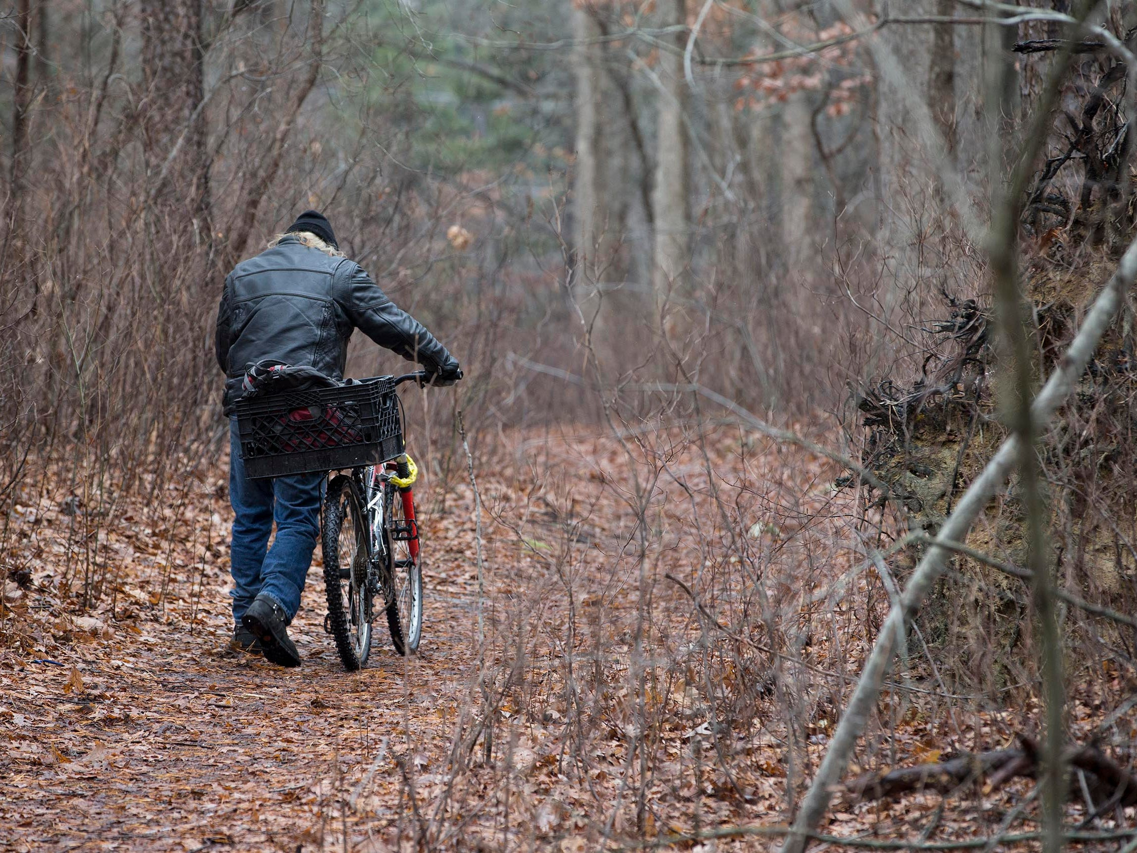 Tim Tiger walks his bike up a hill to get to an appointment.  About one dozen homeless people who live in a small encampment in the woods have been staying at the Crystal Inn since severe cold weather and snow hit the area. Donations collected made the hotel stay possible.  Neptune, NJ on Wednesday, January 17, 2018